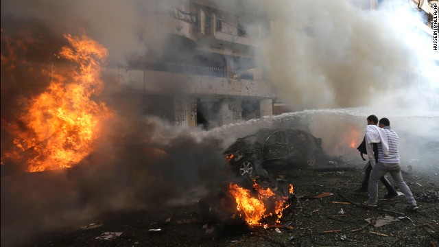Two men watch as cars burn at the scene of the blast.