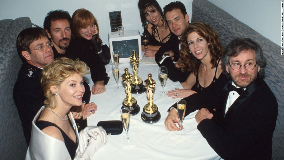 John sits at a table with other celebrities, including actress Kate Capshaw, singer Bruce Springsteen, actor Tom Hanks and director Steven Spielberg, at the Elton John AIDS Foundation Party in 1994. The party was held after the Academy Awards in Los Angeles.