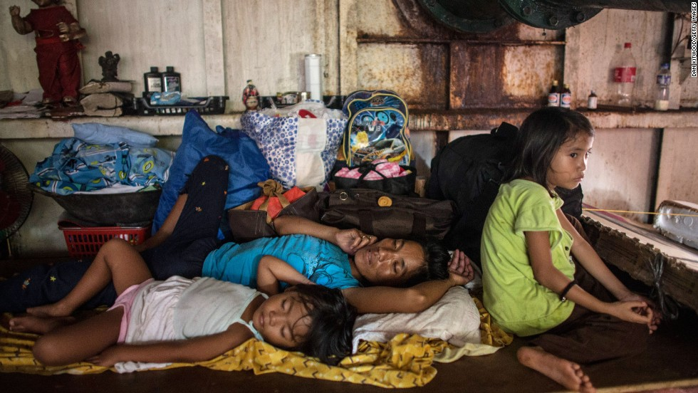 A family rests Tuesday, November 19, in the hull of a tanker run aground during Typhoon Haiyan in Tacloban.