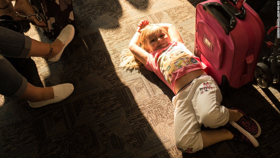 Shannon Nevin, 4, waits with her family at gate A21 for a flight to Savannah, Georgia.