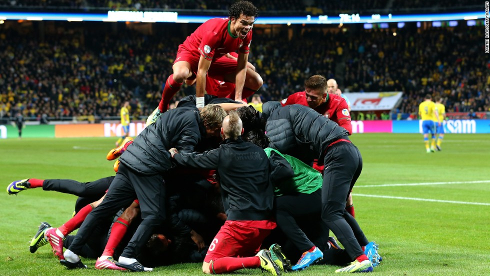 The Real Madrid star is mobbed after his hat-trick seals Portugal's place in the 2014 World Cup.