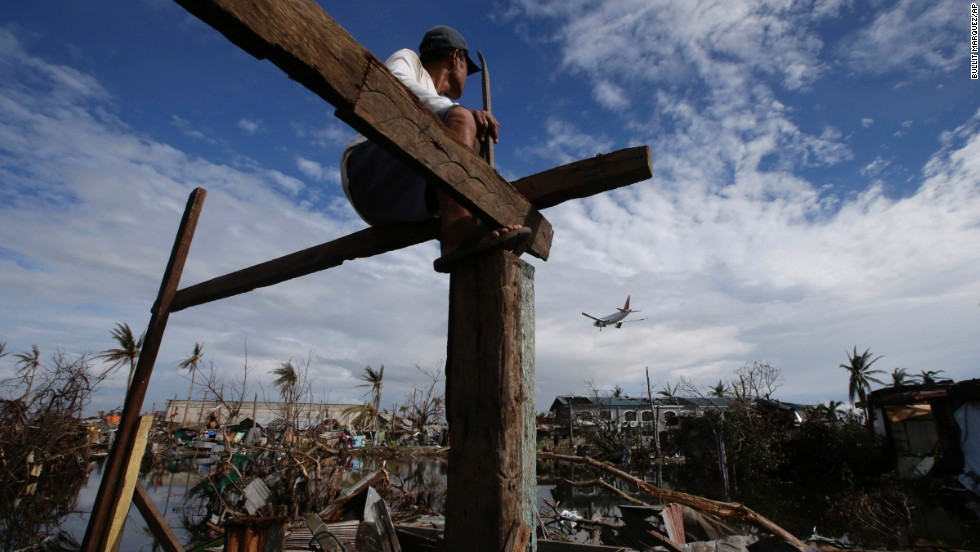 An airplane lands in Tacloban as Antonio Lacasa rebuilds his house on Thursday, November 21.