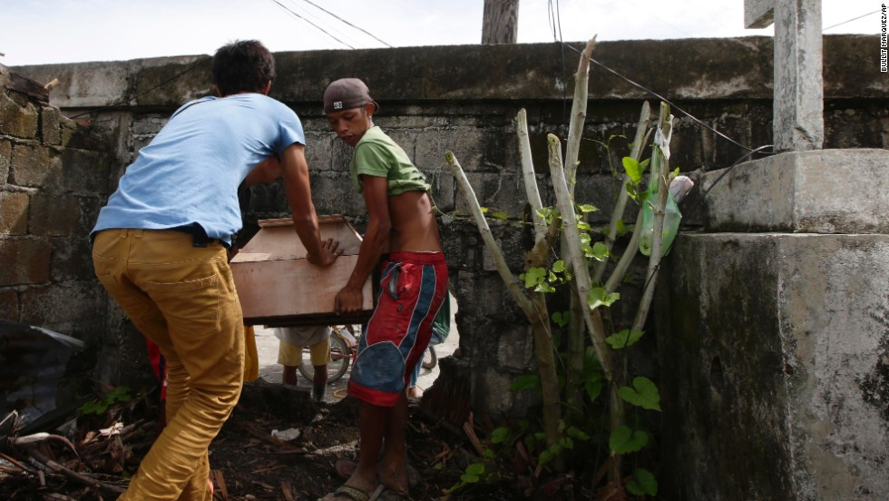 People carry a coffin through an opening in the wall of a public cemetery for burial in Tacloban on November 21.