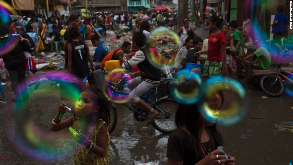 Children blow bubbles in a destroyed market in Tacloban on Wednesday, November 20.