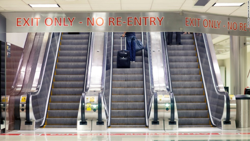 Passengers take the escalator to ground transportation and baggage claim.