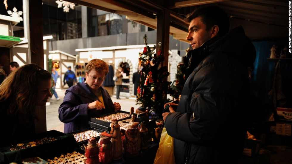 Andriy Shaptala waits on customers at one of his booths at the Denver Christkindl Market downtown.