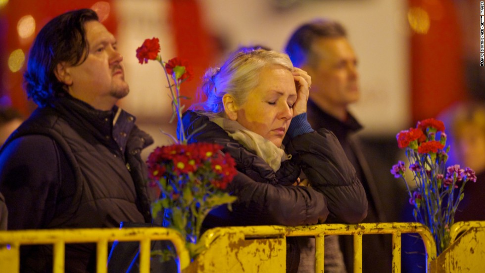 A woman waits for news near a barricade surrounding the supermarket on November 23. Local media reports firefighters are among the dead from the collapse.