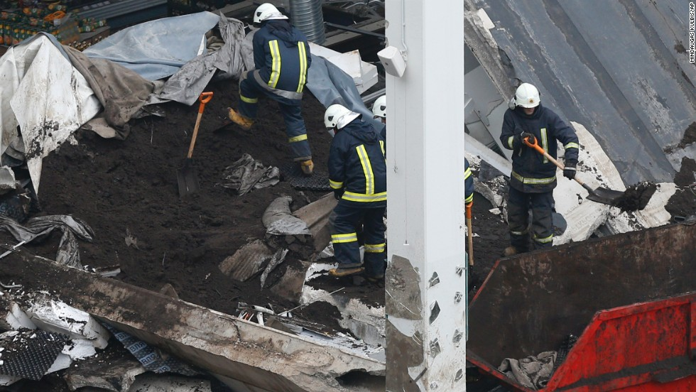 Rescue workers search debris on November 23. Search teams continue to comb the rubble for more bodies, Rescue Service spokeswoman Viktorija Sembele said.