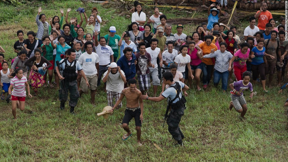 An aerial view on November 23, shows Typhoon Haiyan victims running and waving at a Philippine Air Force helicopter bringing food to La Paz.