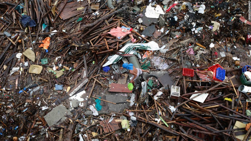 A man searches through the debris in Tacloban on November 23.
