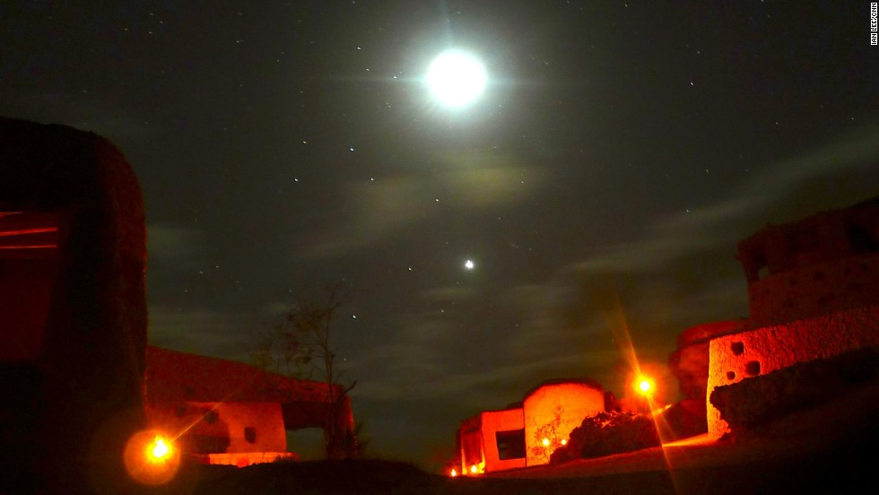 The night sky is illuminated by stars, while the ecolodge is illuminated by lanterns.