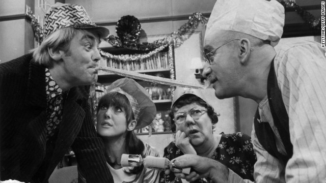 "Alf Garnett (Warren Mitchel) and son-in-law Mike (Anthony Booth) argue during Christmas dinner in the BBC's ""Till Death Do Us Part."""