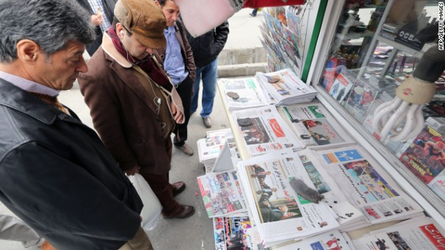 Iranians look at newspapers displayed outside a kiosk on November 24, 2013 in the capital Tehran a day after a deal was reached on the country's nuclear programme.