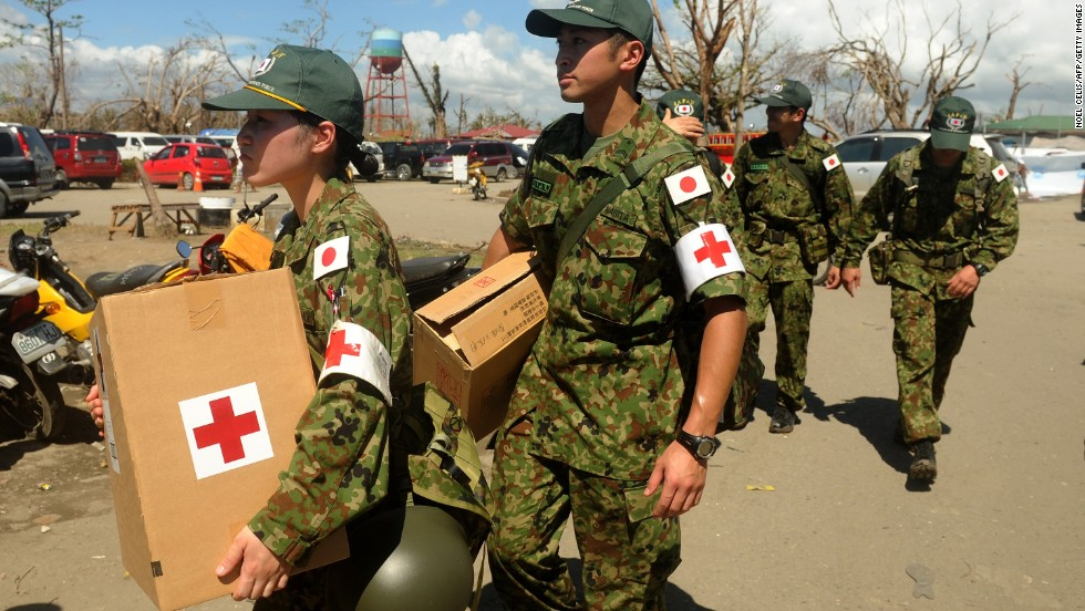 Members of the Japanese Self-Defense Force carry boxes of medicine to be distributed to survivors of typhoon Haiyan in Tacloban on Monday, November 25.