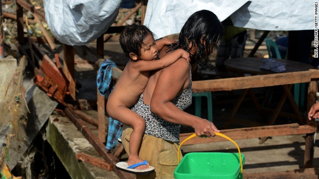 A mother carries her baby through the devastation in Tacloban, Philippines, in November after Typhoon Haiyan.