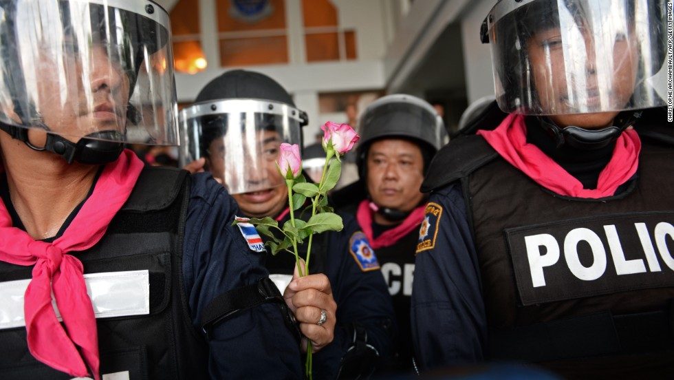 A Thai riot policeman holds flowers which were offered to him by opposition protesters during a rally at a government complex in Bangkok on November 27, 2013.