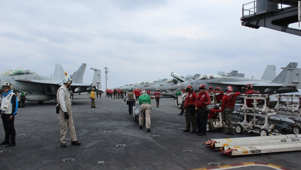 The carrier's flight deck crew -- wearing colored vests according to the duties they perform -- are responsible for flight ops night and day.