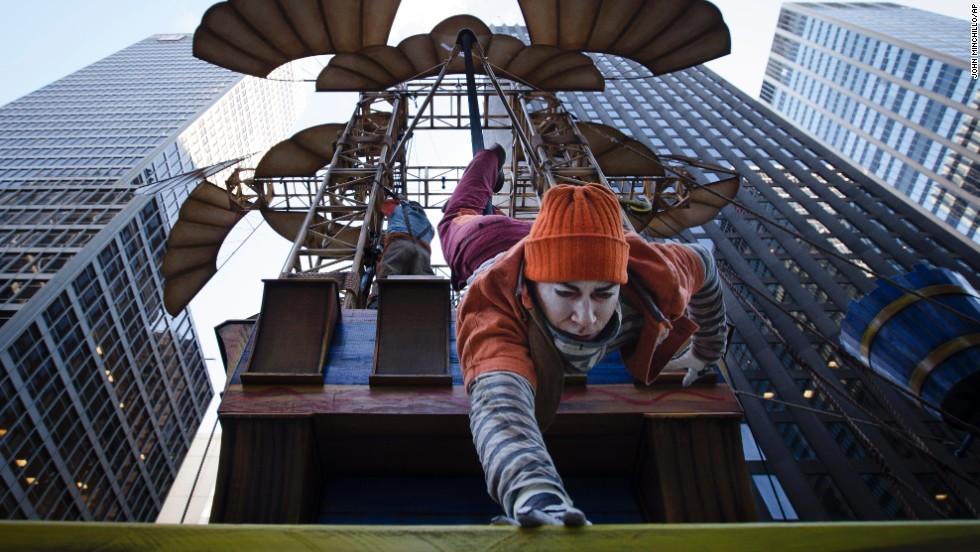 A performer slides down a pole on the Cirque du Soleil float.