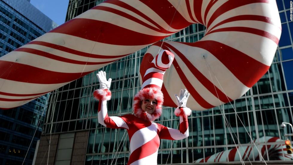 A performer on stilts walks near a candy cane balloon.