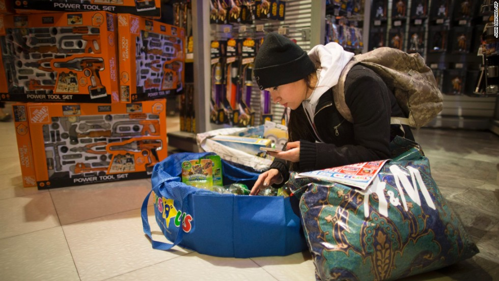 Maggie Salas uses her smartphone to help her shop at the Times Square Toys R Us on November 28.