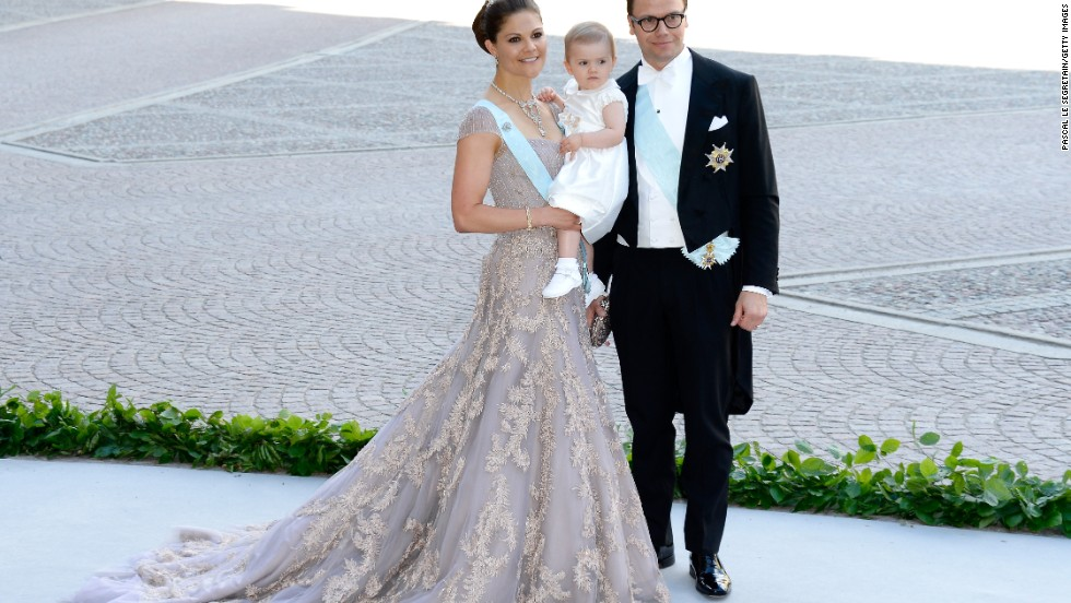 Crown Princess Victoria of Sweden flies the flag for Scandinavian style, often wearing romantic dresses in shimmering pastel hues. Here she is with her daughter Princess Estelle of Sweden, and husband Prince Daniel at the wedding of her sister Princess Madeleine in Stockholm.