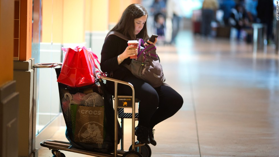 A woman sits on a shopping cart at Miami's Dolphin Mall as she checks prices on her smartphone on November 29.