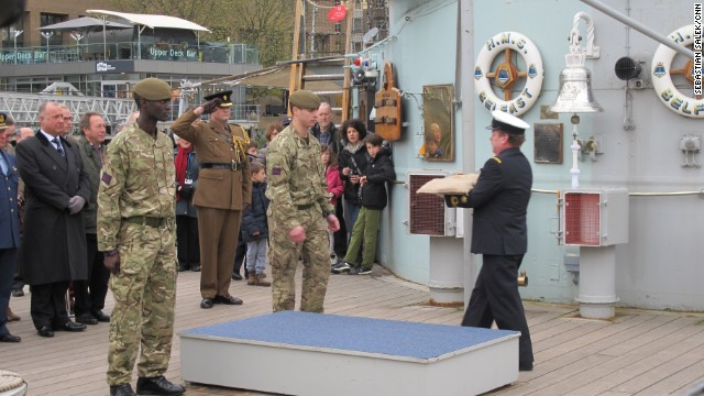 One of the bags of soil is handed over on board HMS Belfast in London