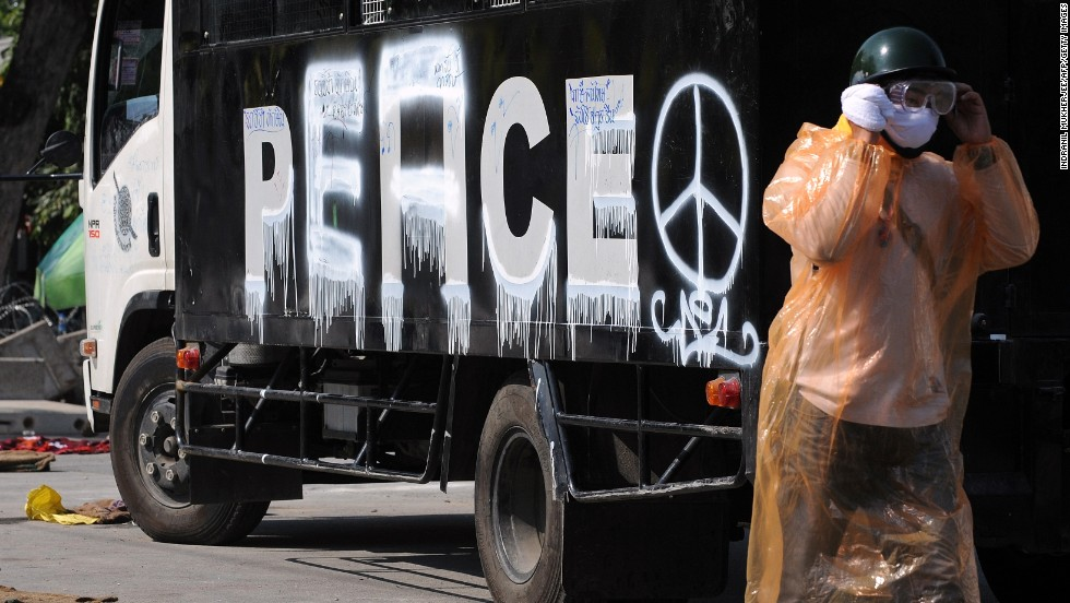 "An anti-government protester walks past a police vehicle with the word ""peace"" painted where ""police"" used to be."