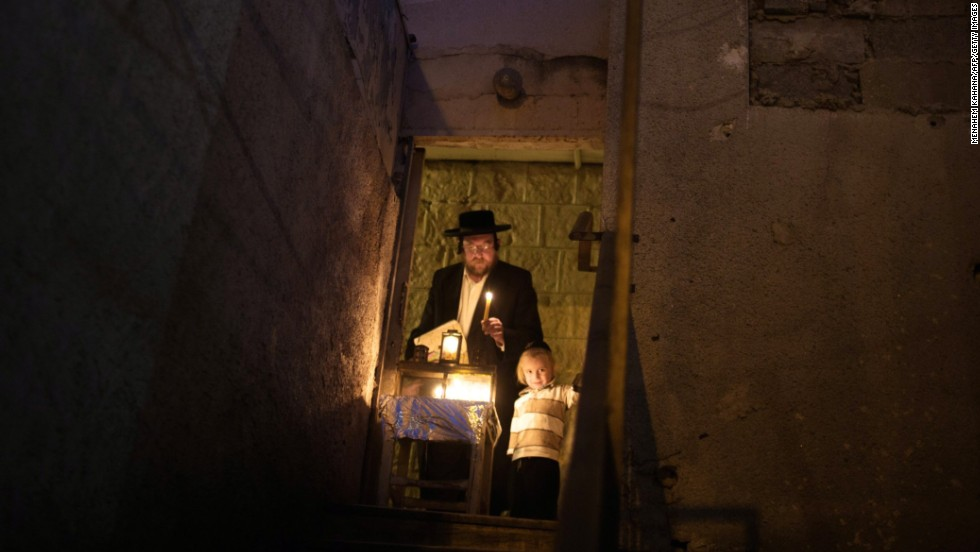"DECEMBER 2 - JERUSALEM: An Ultra-Orthodox Jewish man and his child light candles on the fifth night of the <a href=""http://religion.blogs.cnn.com/2013/11/26/giving-thanks-for-the-miracle-of-survival/"">Jewish holiday of Hanukkah</a>, the Festival of light. The holiday commemorates the victory of the Maccabees over the Syrians and the re-dedication of the Second Temple of Jerusalem around 165 BC after the Greek King of Syria outlawed Jewish rituals."