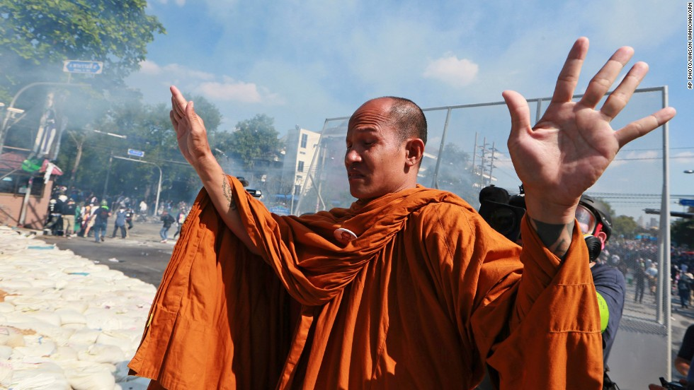 "DECEMBER 3 - BANGKOK, THAILAND: A Buddhist monk raises his hands to policemen in Bangkok. <a href=""http://edition.cnn.com/2013/12/03/world/asia/thailand-protests/index.html?hpt=hp_t2"">Tensions in the capital eased after police took down barricades </a>and allowed anti-government demonstrators to enter the government buildings. Policemen shook hands with demonstrators, ushering them past. Protesters responded with cheers and applause, claiming victory."