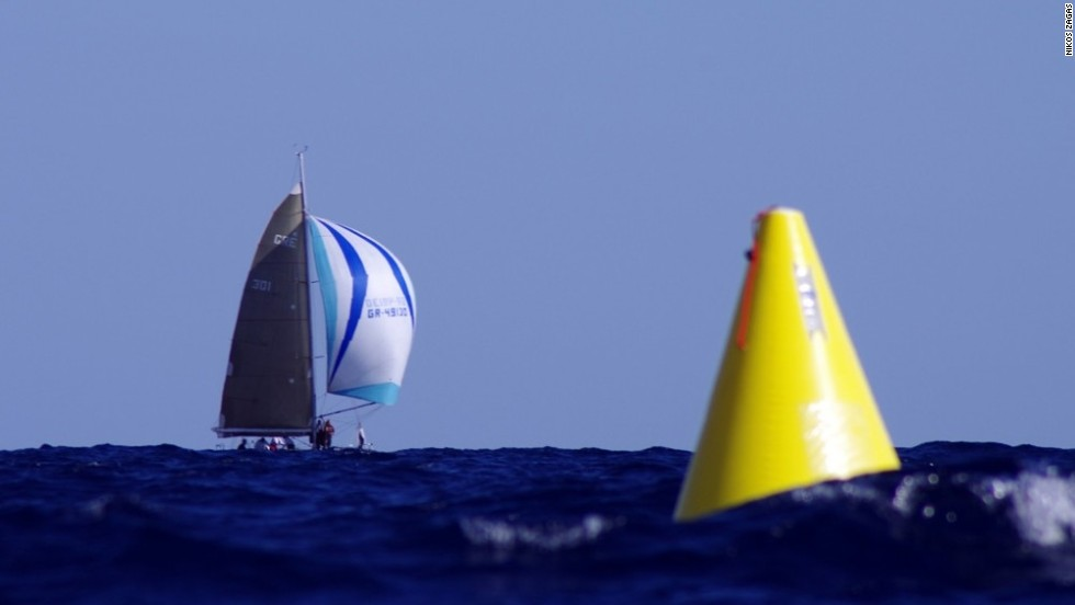An out-of-focus yellow buoy bobs on the surface of the water as, in a distance, Pachakis Ioannis glides over the water in October's Cretan Union Cup, captured on a Pentax 450mm.