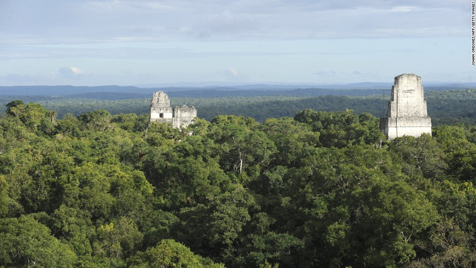 The Mayan temples at Tikal poke above the treeline in the Petén department of Guatemala.