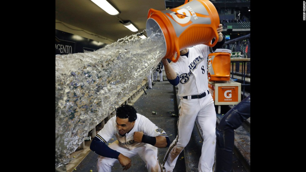 Carlos Gomez of the Milwaukee Brewers ducks out of the way as teammate Ryan Braun tries to soak him with water after a game against the San Francisco Giants on April 17 in Milwaukee. The Brewers won 4-3.