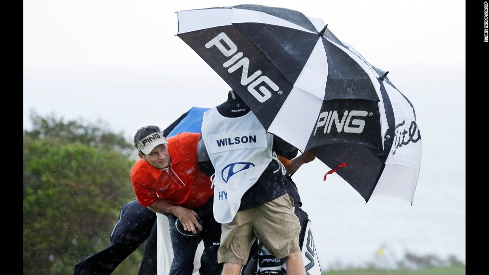 Mark Wilson peers out from under an umbrella as he waits for a rainsquall to ease up before teeing off on the 10th hole during the first round of the PGA Tournament of Champions on January 7 in Kapalua, Hawaii. Play was supposed to start three days earlier but was delayed because of rain and high winds.