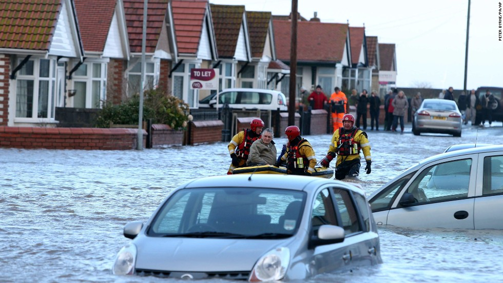 A rescue team helps a man across floodwaters in Rhyl on December 5.