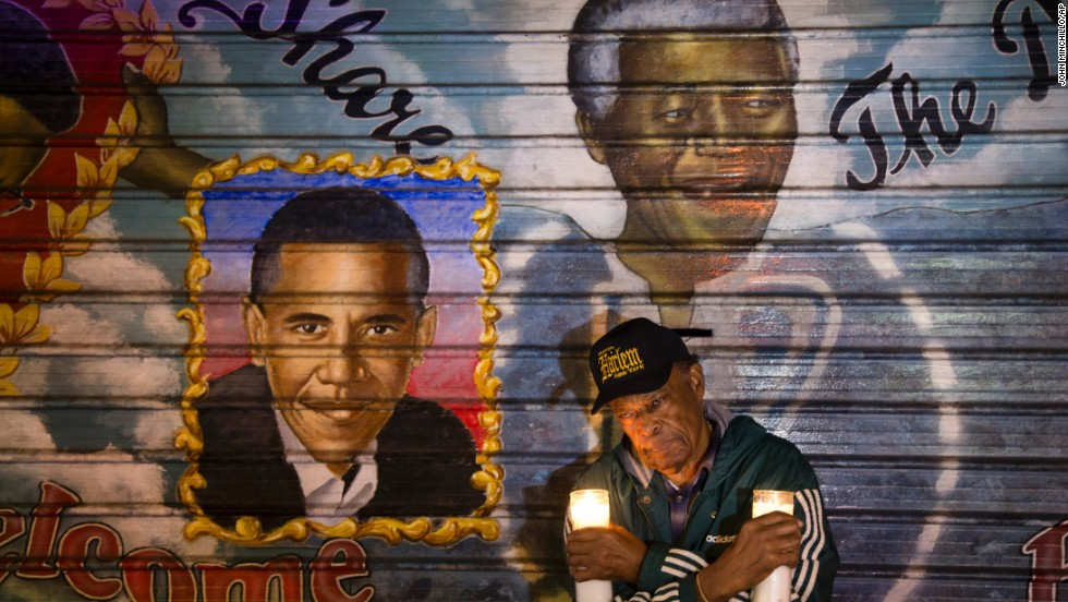 An artist who goes by the name Franco the Great stands beneath a Mandela mural that he painted in New York's Harlem neighborhood more than 15 years ago. He later added Obama to the mural.