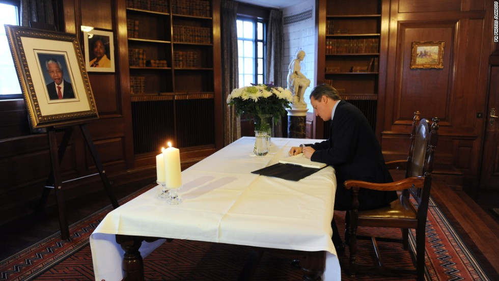British Prime Minister David Cameron signs the book of condolence at the South African Embassy in central London following the announcement of Mandela's death.