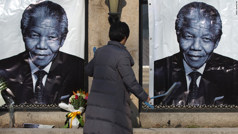 A woman cleans up outside the South African Embassy in Beijing where portraits of Mandela and flowers offered by people are placed on December 6.