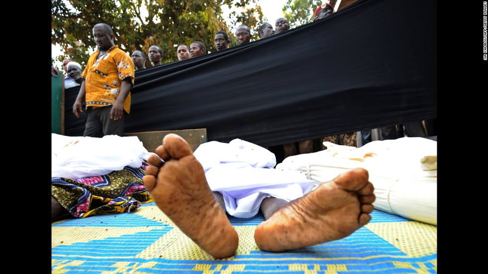 People stand near bodies found lying in a mosque and in its surrounding streets in Bangui on December 5.