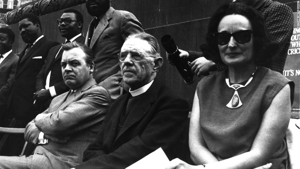 Ruth First (left) was an anti-apartheid activist and investigative journalist. She was exiled from South Africa in 1964, with her husband, prominent South African communist Joe Slovo, and their children. In 1982, while working in Mozambique, First was killed by a letter bomb sent by the South African secret service. First is seen here at the Anti-Apartheid Movement's freedom day rally in London in 1965.