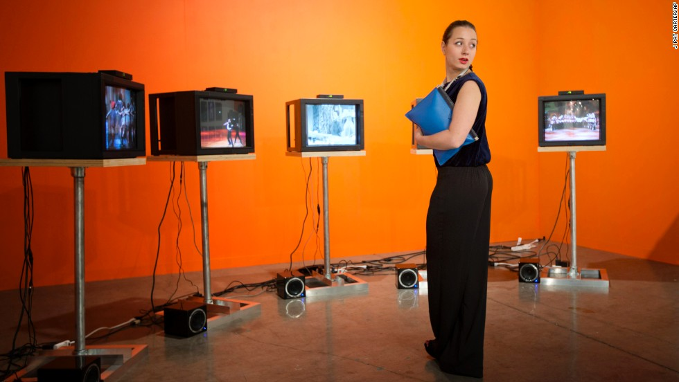 "Marina Kurikhina, a Russian art adviser who lives in London, studies a Charles Atlas video installation at Art Basel Miami Beach 2013 on December 4. The video consists of five screens showing a five-channel synchronized work called ""Martha, Martha, Martha, Martha, Martha."""