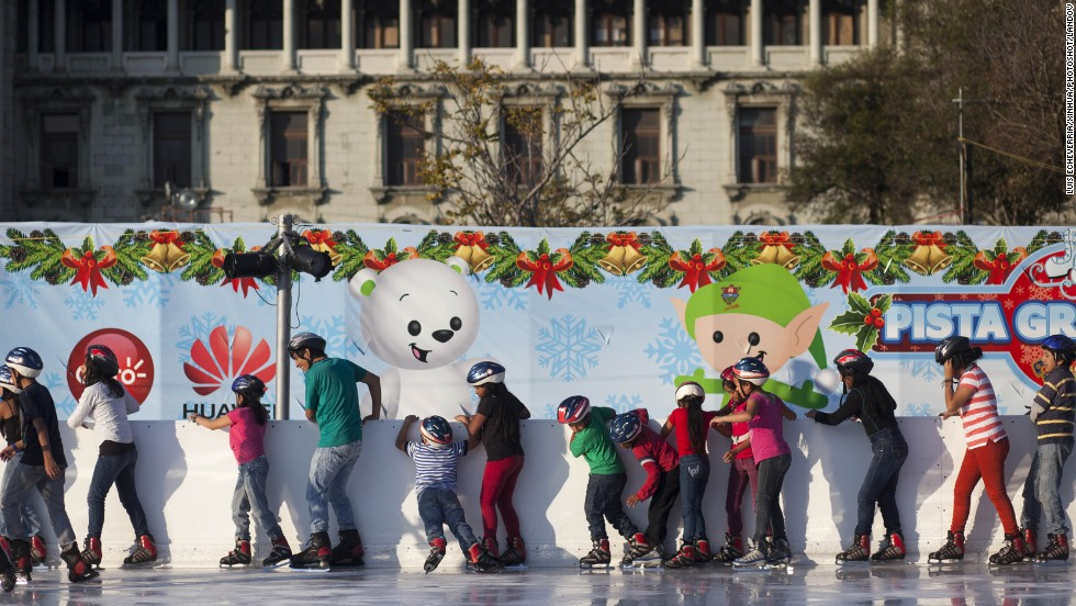 Young skaters in Guatemala City, Guatemala, hold on to a wall as they skate on an ice ring installed at Constitution Square on December 4.