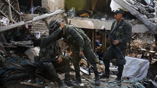 Colombian soldiers walk amid rubble of a police station following a car bombing, in Inza , department of Cauca, Colombia, on December 7, 2013.