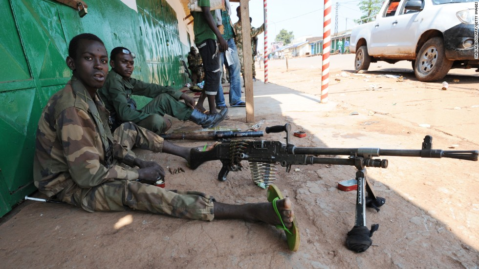 A former member of the militia that led the coup against the Central African Republic's president sits next to a machine gun as he and others stand guard at a shut-down market in Bangui on December 7.