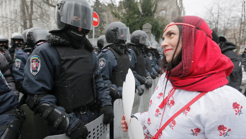 A pro-EU activist holds a cut-out paper heart as she faces police at the presidential office in Kiev on December 8.