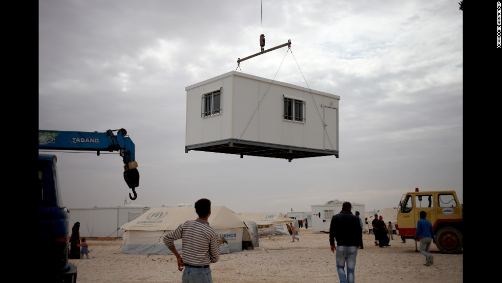 Refugees watch a new trailer being placed in the Zaatari camp on December 3.