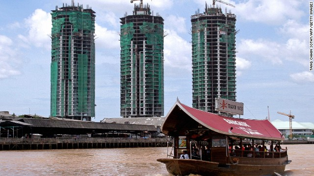 A boat sails past a construction project on Bangkok's Chao Phraya river.