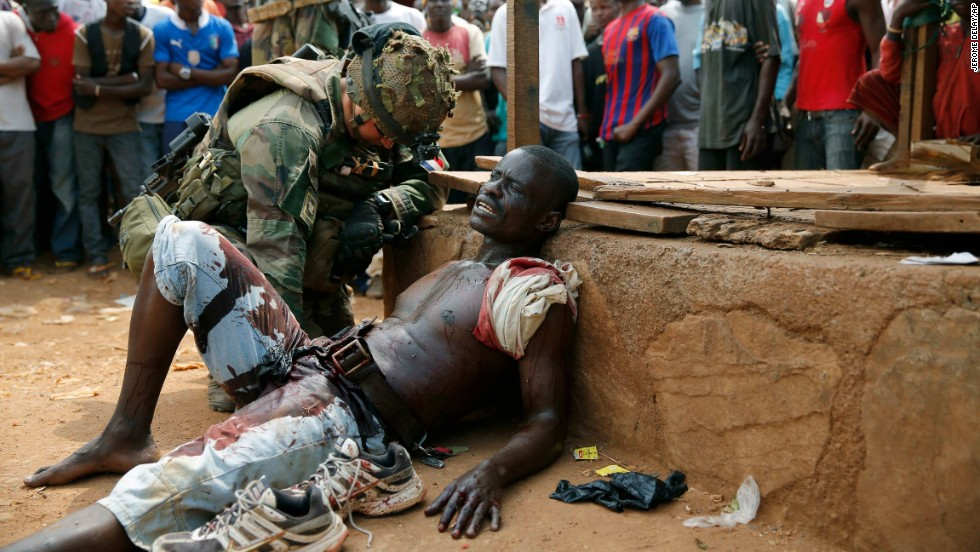 A French soldier speaks to a suspected Christian militia member who was wounded by a machete in the Kokoro neighborhood of Bangui on December 9. Vigilante crowds said they spotted him with grenades and turned him in to French forces.