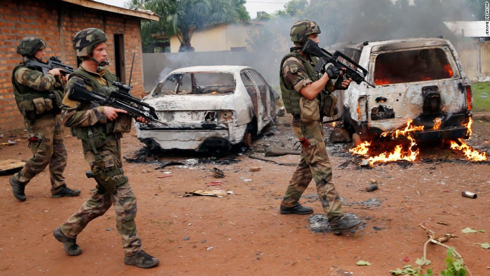 French troops walk past two Seleka vehicles suspected of being set on fire by Christian mobs in Bangui.