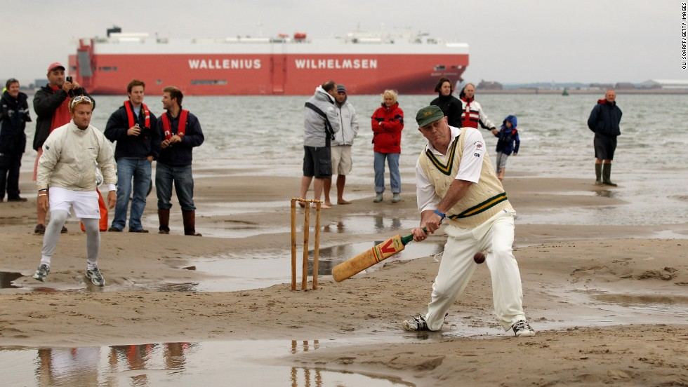 Massive container ships pass in the background, while other smaller vessels also get a close view of the temporary cricket wicket.
